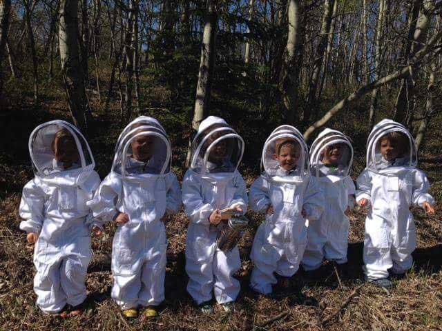 Des enfants en tenues d'apiculteurs